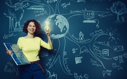 Female teacher holding solar panel and flashing light bulb --- Image by © Ben Hupfer/Corbis