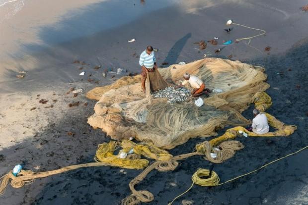 Pescadores inspecionam suas redes em Varkala, Kerala.- FOTO DE FRANK BIENEWALD, GETTY IMAGES