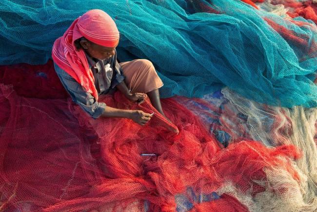 Um pescador em Kerala, Índia, conserta redes na praia. A poluição plástica pode danificar obstruir as redes, mas agora os pescadores estão reagindo. FOTO DE FRANK BIENEWALD, GETTY IMAGES