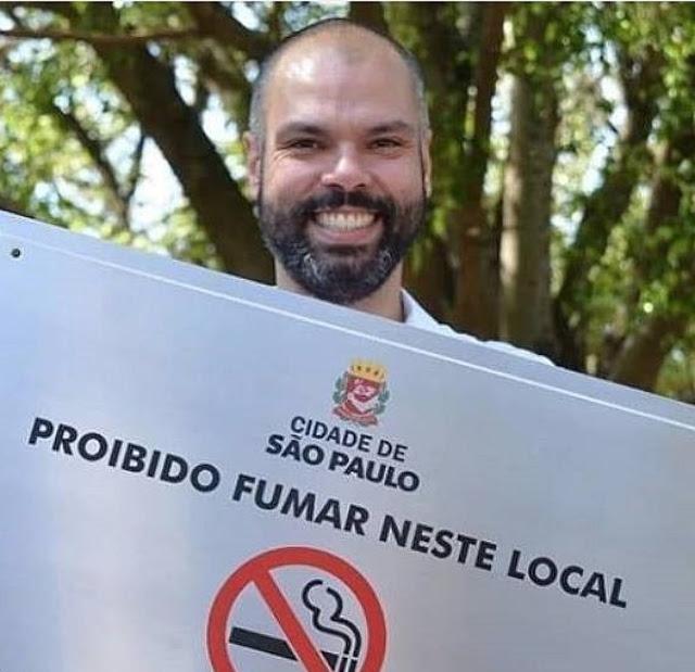 O alcaide tucano Bruno Covas com placa proibindo fumar nas praças e parques de São Paulo