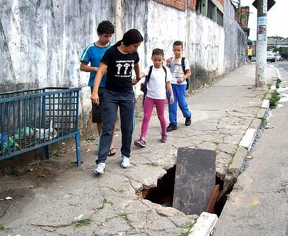 Pedestres tem que driblar buracos, lixeiras, etc, nas calçadas.