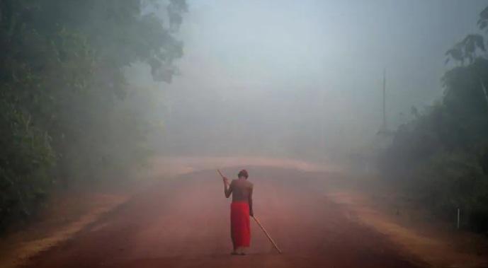 O chefe tribal Tzako Waiapi anda pelo nevoeiro na aldeia Manilha na reserva indígena de Waiapi no estado do Amapá, Brasil. Tribos indígenas que nunca foram contatadas são raras na Amazônia e há muito debate sobre fazer ou não contato com as que ainda restam.(foto de Apu Gomes, AFP/Getty Images)