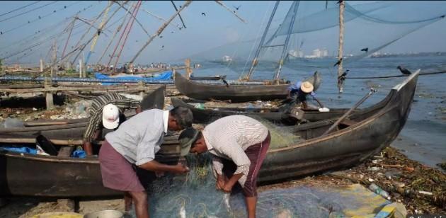 Pescadores em Kochi (também conhecido como Cochin) em Kerala separam o que pescaram.- FOTO DE KAVEH KAZEMI, GETTY IMAGES