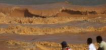 Homens observam uma onda de lama se quebrar na praia em Regência (Foto: Ricardo Moraes/Reuters)