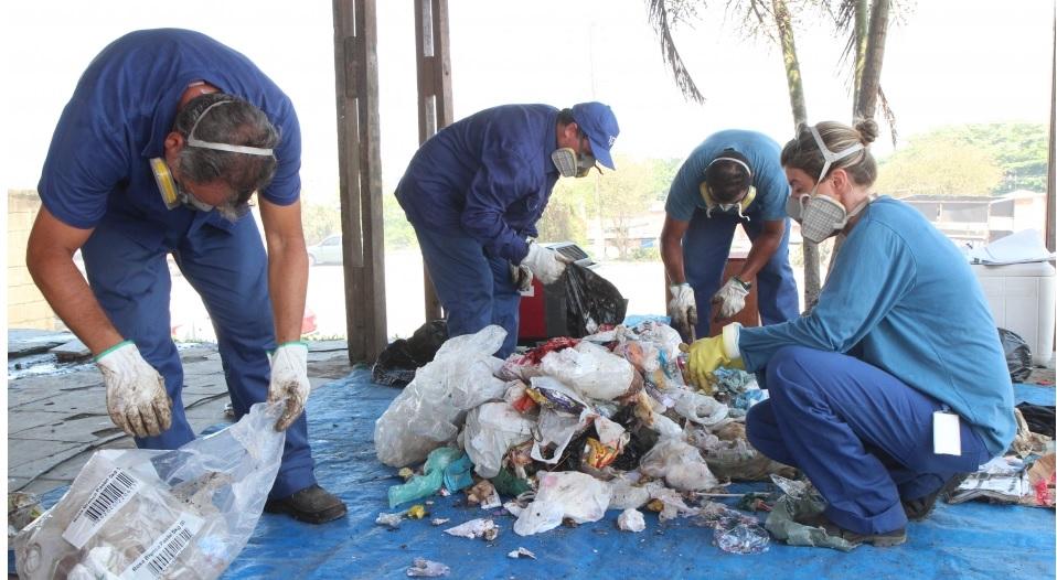 Resíduos são despejados sobre uma outra lona e, nesse momento, os sacos menores são abertos; resíduos são então separados em recicláveis, orgânicos e rejeitos