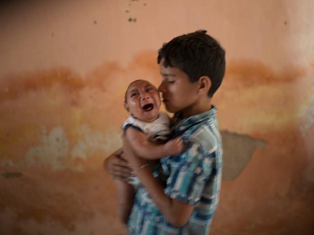 Foto de 23 de dezembro mostra menino Elison, de 10 anos, cuidando de seu irmão de 2 meses José Wesley, que nasceu com microcefalia, em Poço Fundo, no Pernambuco (Foto: AP Photo/Felipe Dana) no G1