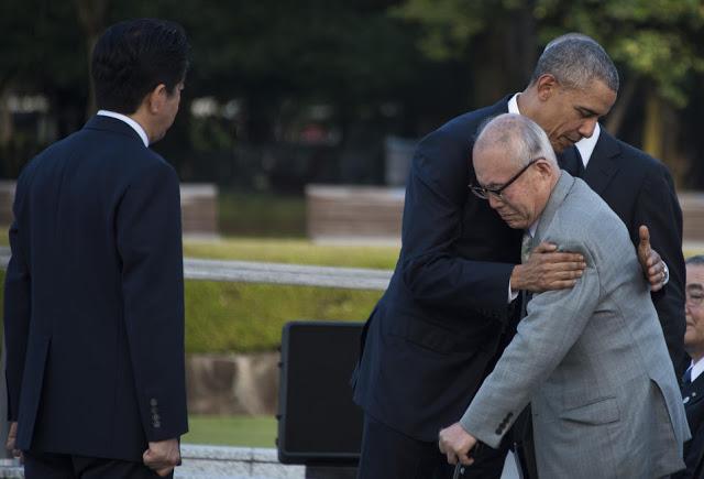 Barack Obama abraça Shigeaki Mori, um sobrevivente do ataque nuclear, que se levantou para cumprimentá-lo no Parque da Paz, em Hiroshima. Testemunhando o fato histórico, o atento Primeiro Ministro do Japão, Shinzo Abe (foto: Jim Watos / Getty Images)
