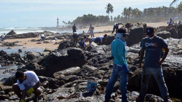 Com Farol de Itapuã ao fundo, voluntários trabalham na limpeza do óleo em Salvador (Direito de imagemVICTOR UCHÔA/BBC NEWS BRASIL)