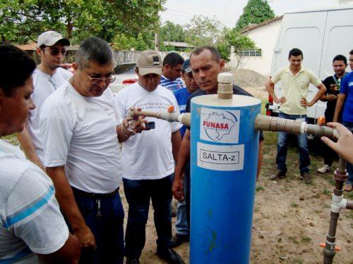 Técnicos da Funasa explicando funcionamento do filtro em comunidade quilombola.