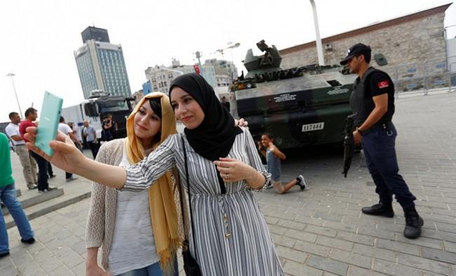 Turistas argelinas fazem uma selfie em frente a um tanque abandonado - golpe para turista ver...